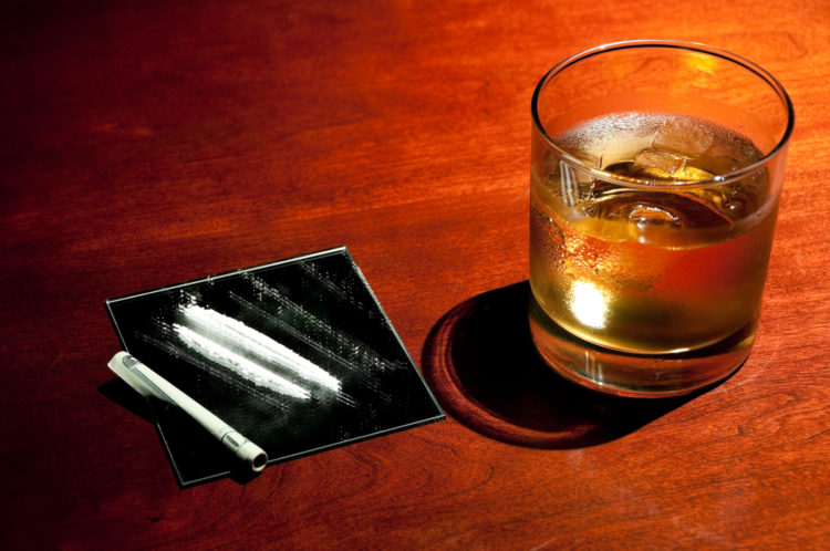 Well drink, could be Rum or whisky along with simulated cocaine on a wooden table with a rolled up twenty dollar bill.